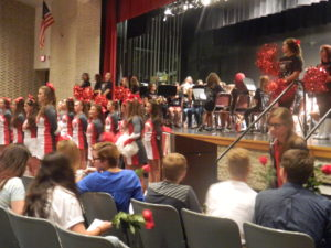 The 2016-2017 student council sits in the foreground as cheerleaders accompany the band while students enter the assembly