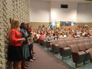 Vice Principal Dwulit, with new paraprofessional Mrs. Simmons and long-term math substitute Mrs. Patterson to her right, listen to additional staff introductions during the assembly