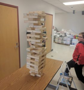 Students like _________________ kid on right took advantage of the Jenga tower station with Mr. Wolfe to build this tower. The Jenga activity was one of a number of new activities outside of the auditorium connected to the auction, including a flag football game, basketball game, cornhole, and Madden gaming.